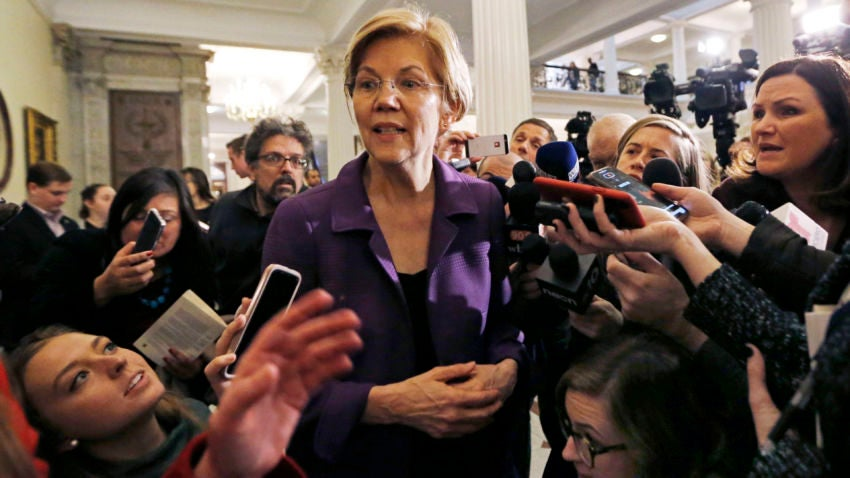 Sen. Elizabeth Warren, D-Mass., is surrounded by reporters at the Massachusetts Statehouse, Wednesday, Jan. 2, 2019, in Boston. Warren has taken the first major step toward launching a widely anticipated campaign for the presidency, hoping her reputation as a populist fighter can help her navigate a Democratic field that could include nearly two dozen candidates. (AP Photo/Elise Amendola)