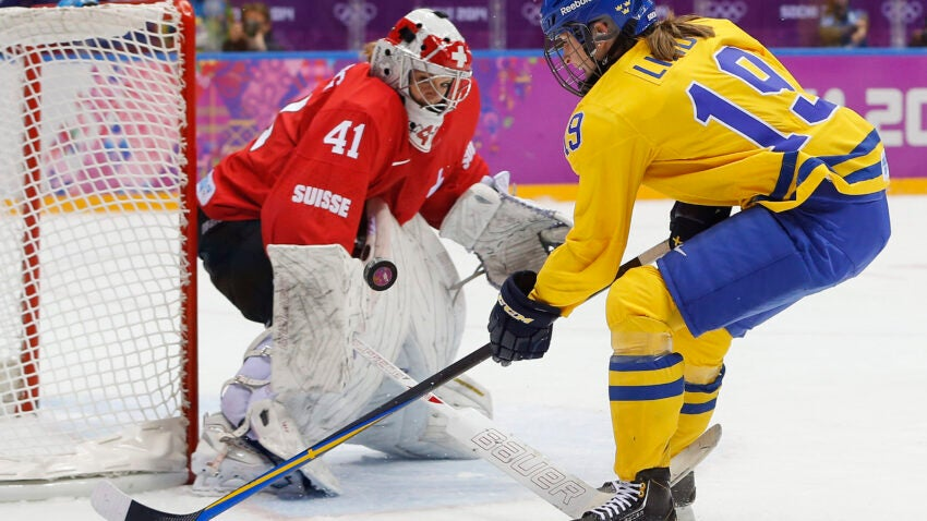 Goalkeeper Florence Schelling of Switzerland (41) blocks a shot by Maria Lindh of Sweden (19) during the first period of the women's bronze medal ice hockey game at the 2014 Winter Olympics, Thursday, Feb. 20, 2014, in Sochi, Russia. (AP Photo/Mark Humphrey)